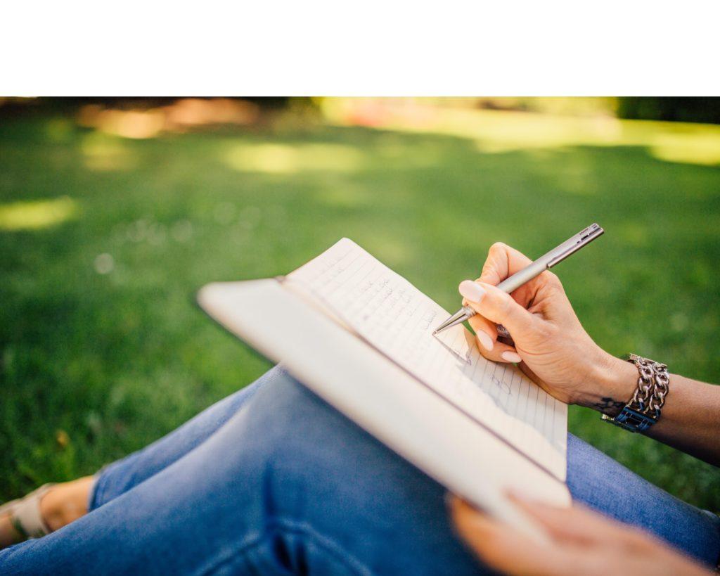 Femme qui écrit dans un parc - Rédaction et rédaction web par Erialla Communication