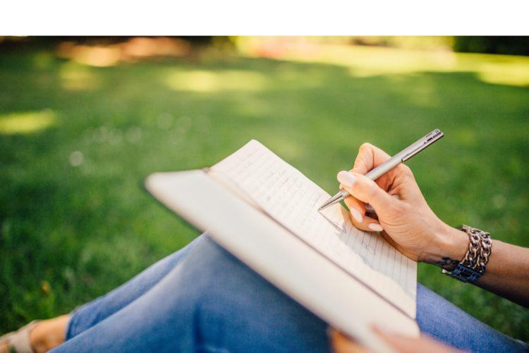 Femme qui écrit dans un parc - Rédaction et rédaction web par Erialla Communication à Auray