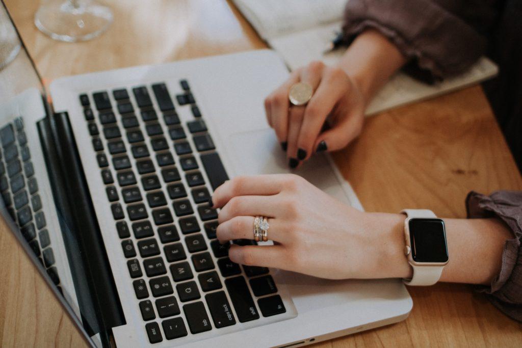 Femme écrivant sur ordinateur - Rédaction et rédaction web par Erialla Communication